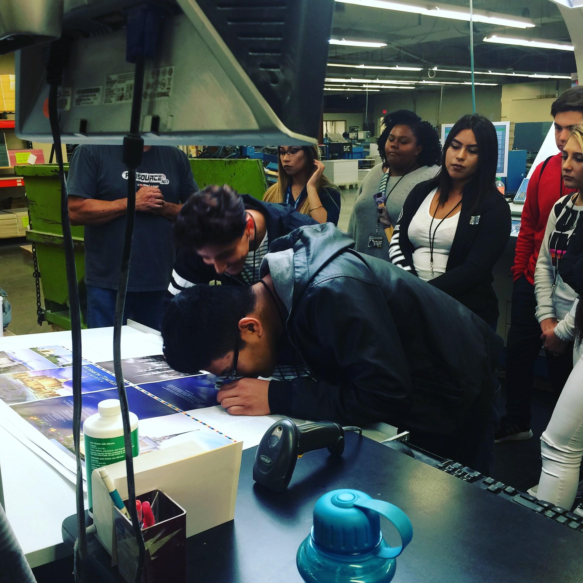 Media students looking at printing proofs at Jostens factory.