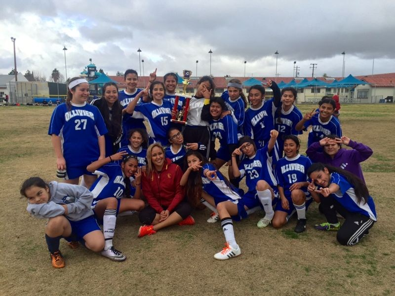 The Ollivier Middle School soccer team holding a trophy