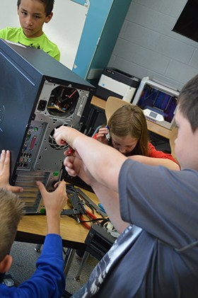 Lee students work on taking apart a computer in the makerspace room.