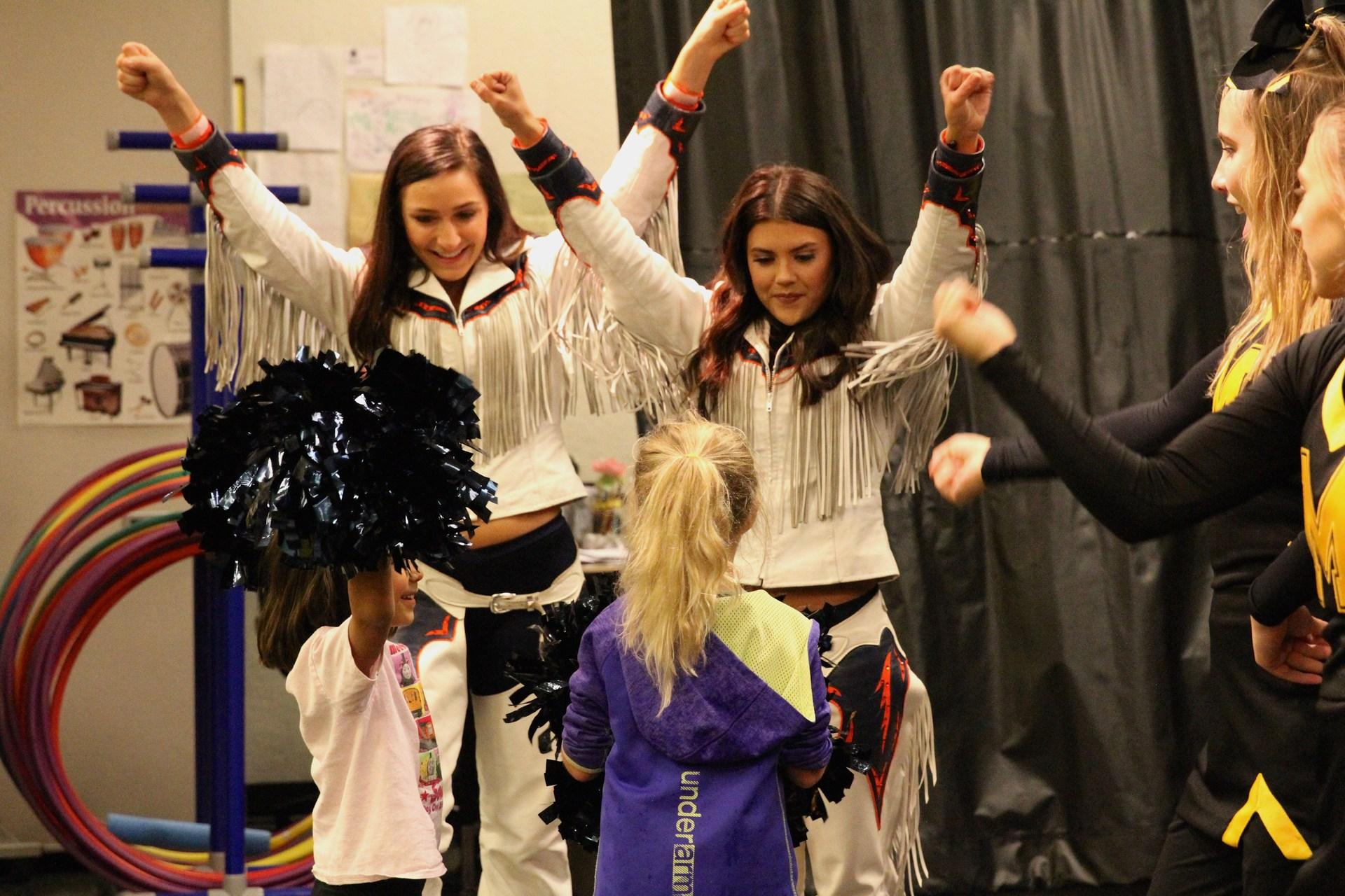 Broncos cheerleaders show little girls a cheer