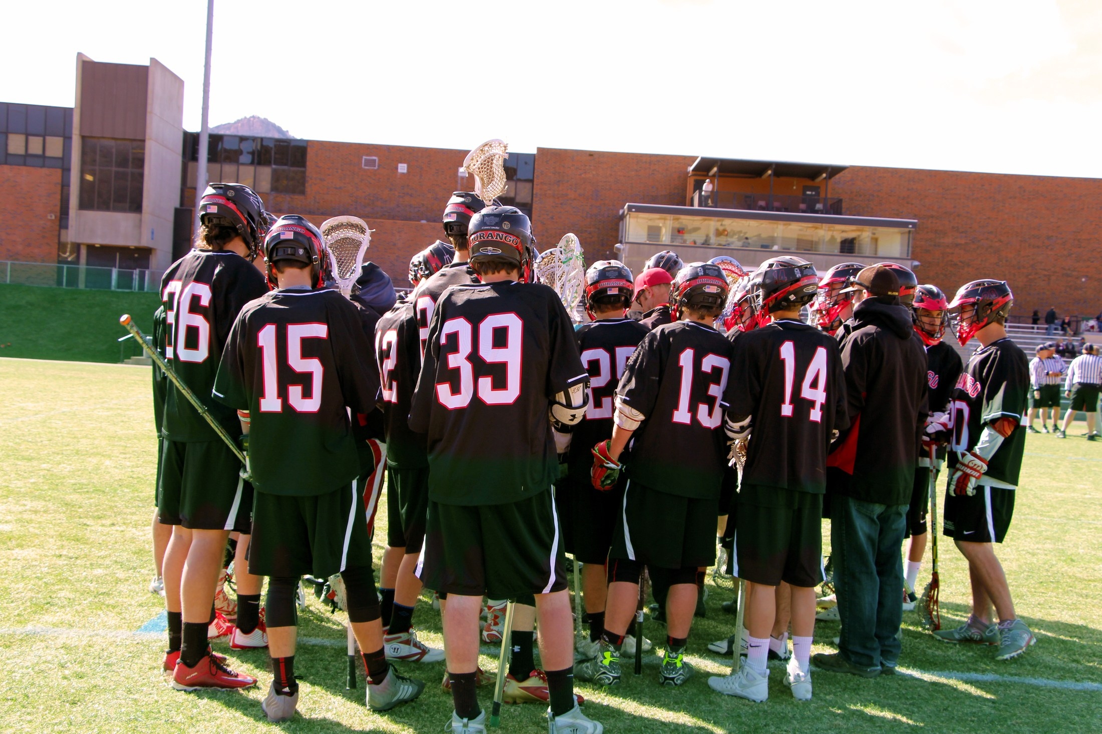 DHS Boys Lacrosse team gathers up in a huddle at half time.