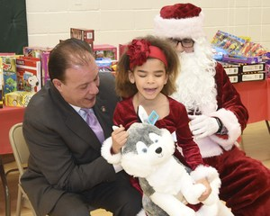 Assembly Member Mark Gjonaj with Santa and an Institute child getting a present