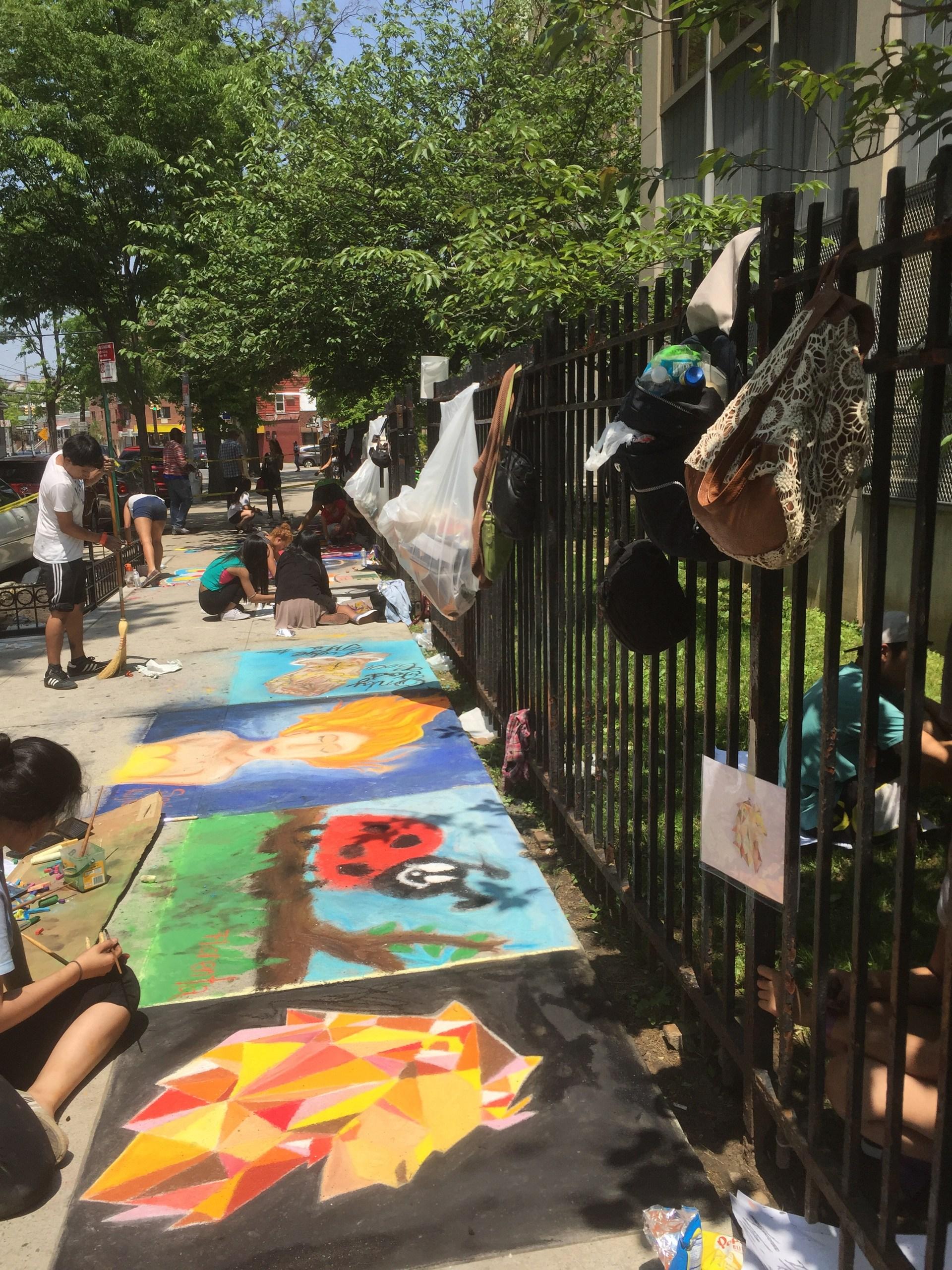 Students drawing on sidewalk.