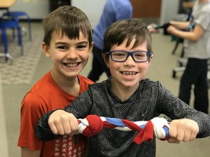 Elliot DeVries (l) and Liam Lietz show off the braided chew toy they made.