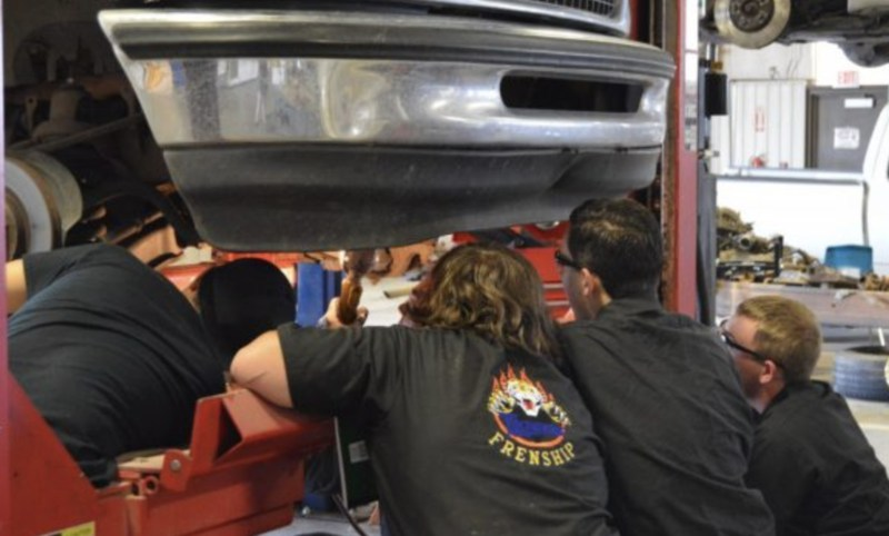 Automotive students looking underneath a lifted truck