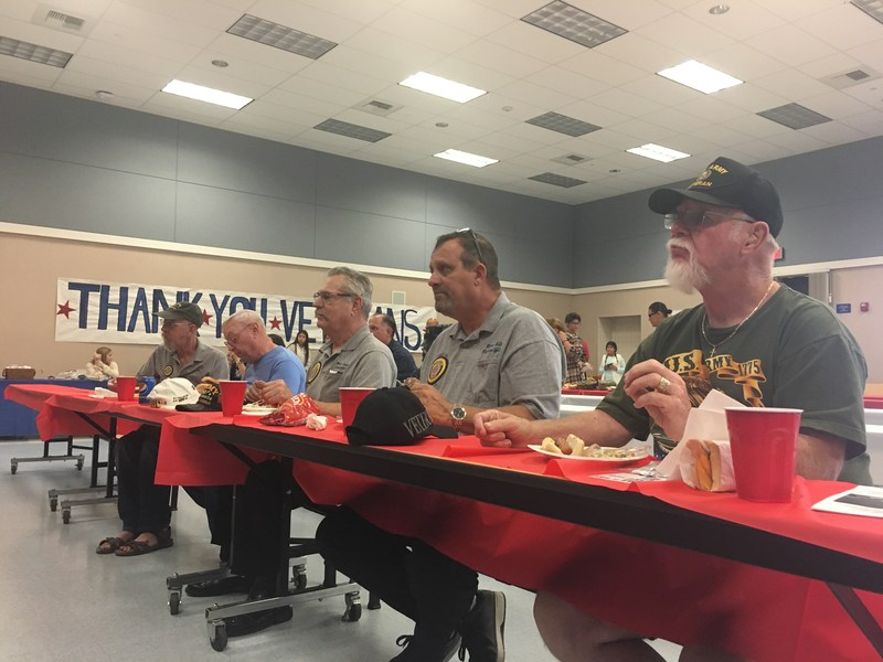 Local Veterans sitting at a table eating.