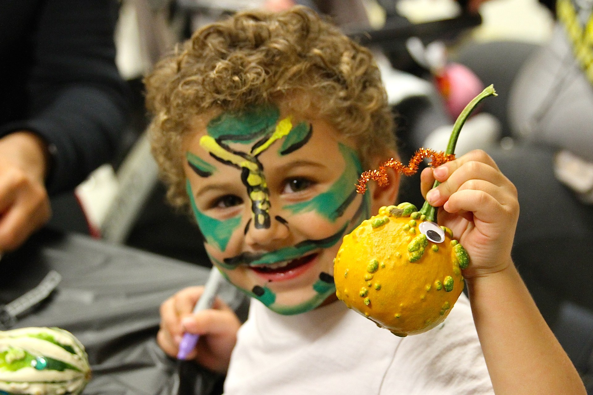 child with face paint holding up decorated gourd